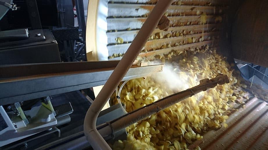 Распыление смеси специй на чипсы в барабане
